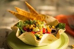 Auf dem Foto erkennt man eine Schale aus einer Tortilla, die mit den Zutaten eines Tacos gefüllt ist, also Salat, Mais, Zwiebeln und roter und gelber Paprika. Außerdem sind drei Nachos im hinteren Teil der Schale in die Füllung gesteckt worden. Die Schale steht auf einem hell-grünen Teller auf eiem Holztisch. Im Hintergrund auf der rechten Seite erkennt man eine rote Serviette mit einer Gabel drauf.