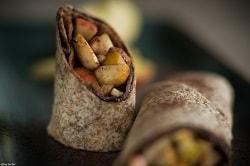 Auf dem Foto erkennt man die Vollkorn-Tortilla von MTG Foodtrading als Wrap. Ein Wrap liegt dabei mit der geöffneten Seite zum Zuschauer gewandt und ein halber Wrap steht, wobei seine geöffnete Seite nach oben schaut. Der Wrap ist mit Apfelstückchen befüllt. Die Wraps sind auf einem schwarzen Tablett abgebildet.