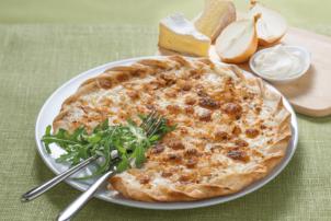Auf einem weißen Teller liegt ein Flammkuchen von Maitre Pierre. Der Flammkuchen ist mit Zwiebeln und Camembert belegt und goldb-braun gebacken worden. Auf dem Teller sind außerdem noch Kräuter zu sehen, die der Dekoration dienen. Neben Besteck befindet sich auf dem grünen Tisch noch ein Schneidebrett mit Zwiebeln und Camembert.
