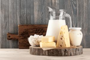 Eine Glaskanne mit Milch, Frischkäse, Quark im Glas und zwei verschiedene Sorten Käse liegen auf einer Holzplatte. Die Milchprodukte stehen vor einer Holzwand und einem dunklen Schneidebrett auf einem hellen Holzboden.