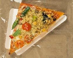 Auf dem Foto ist eine dreieckige Pizza abgebildet. Es ist der Point Snack vom Pizzahersteller Point of Food. Die Pizza ist belegt mit Gemüse wie Cherrytomaten, Bohnen und Mais, aber hauptsächlich mit Quinao. Deshalb ist es auch die gesunde Variante des Point Snacks, der Point Fitpizza Snack. Die Pizza ist auf einem dreieckigen Pappslice in einer Verpackung zu sehen. Man erkennt, dass diese Pizza sich in einer Verpackung befindet, durch die Klarsichtfolie und den braunen Tüten-haftigen Hintergrund.
