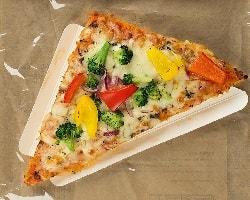 Auf dem Foto ist eine dreieckige Pizza abgebildet. Es ist der Point Snack vom Pizzahersteller Point of Food. Die Pizza ist belegt mit Gemüse aller Art wie gelber Paprika, roter Paprika, Zwiebeln und Brokkoli. Diese Variante des Point Snacks nennt sich Verdura. Die Pizza ist auf einem dreieckigen Pappslice in einer Verpackung zu sehen. Man erkennt, dass diese Pizza sich in einer Verpackung befindet, durch die Klarsichtfolie und den braunen Tüten-haftigen Hintergrund.