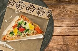 """Auf dem Foto ist eine dreieckige Pizza abgebildet. Es ist der Point Snack vom Pizzahersteller Point of Food. Die Pizza ist belegt mit Gemüse aller Art wie gelber Paprika, roter Paprika, Zwiebeln und Brokkoli. Diese Variante des Point Snacks nennt sich Verdura. Die Pizza ist auf einem dreieckigen Pappslice in einer Verpackung zu sehen. Man erkennt, dass diese Pizza sich in einer Verpackung befindet. Oberhalb der braunen Tütenverpackung steht in schwarzer Schrift """"We love Pizza"""" mehrmals in einem runden KReis geschrieben. Die verpackte Pizza befindet sich auf einem dunkel-grauen Teller auf einem Holztisch."""