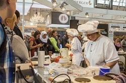 Rechts auf dem Foto erkennt man Fachleute aus der Bäckerbranche. Sie kntene Teig und backen etwas. Sie haben weiße Schürzen und weiße Kochmützen auf. Es sind zwei Frauen. Auf der Messe, der Südback, haben Messebesucher die Möglichkeit Fachleuten bei ihrer Arbeit zuzugucken, deshlab erkennt man auch im Hintergrund und links Menschen, die den Bäckerinnen zugucken.