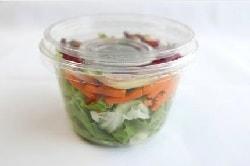 Auf dem Foto ist ein Salat to-go zu sehen. Ein bunter Salat aus Eisbergsalat, Karotten und Bohnen ist in einem durchsichtigen kleinen Becher mit Deckel verpackt.