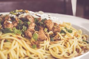 Auf dem Bild ist ein Teller Spaghetti zu erkennen. Auf dem Berg schnell zubereiteter Nudeln befindet sich klein geschnittenes Fleisch, welches kurz angebraten wurde, und klein geschnittener Lauch. Die Mahlzeit ist auf einem weißen Teller angerichtet.