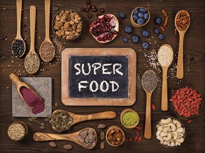 """Ein Schild auf dem """"SUPER FOOD"""" steht. Um das Schild herum sind einige Löffel mit Nüssen und Früchten"""