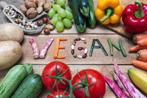 """Auf dem Foto ist mit verschiedenen Gemüsesorten das Wort """"vegan"""" auf einem Holzfußboden ausgelegt. Um den Schriftzug herum befindet sich Obst und Gemüse, wie zum Beispiel Tomaten und Zucchini in der unteren Bildhälfte und Paprika, Zucchini, Nüsse und Weintrauben in der oberen Hälfte des Bildes."""