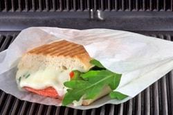 Auf dem Foto ist ein Panini abgebildet, welches in der Verpackung von ELAG - dem OVENBAG - gegrillt bzw. erhitzt wird. Das Panini in der hitzeresistenten Verpackung hat oberhalb schon Grill-muster erhalten und man erkennt den Käse vorne hinaus laufen. Links vom Panini rutscht noch ein Salatblatt hinaus.