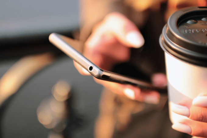 Eine Hand von einer Person hält ein Smartphone. In der anderen Hand ist ein weißer Kaffeebecher mit einem schwarzen Deckel zu sehen. Der Hintergrund ist verschwommen.