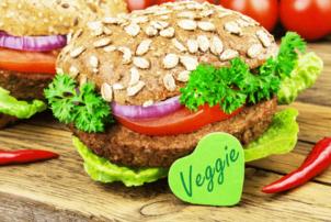 Auf dem Foto ist ein Brötchen mit einem vegetarischem Patty, Salat, Tomaten und Zwiebeln zu sehen. Das Brötchen ist ein Körnerbrötchen. Vor der belegten Backware ist ein grünes Herz angelehnt, auf dem veggie drauf steht,