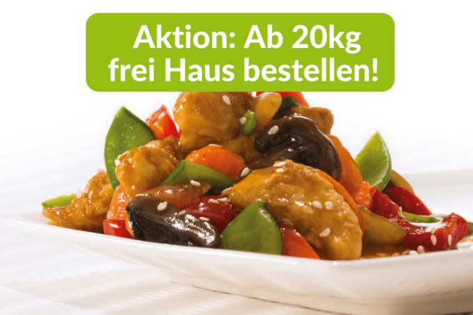 """Auf dem Foto erkennt man das asiatische Gericht Hühnchen Teriyaki von dem Asia-Food-Spezialisten Delasia. Neben Hühnchen ine iner gelb-braunen Soße erkennt man auf dem weißen Teller noch grüne Bohnen und anderes Gemüse, unter anderem auch rotes Gemüse, welches sich jedoch nicht direkt identifizieren lässt. Auf grünem Hintergrund in weißer Schrift steht über dem Convenience-Gericht """"Ab 20kg frei Haus bestellen"""". Dies ist eine Aktion von snackconnection, die darauf hinweist, dass ab einer Erstbestellung von 20kg der Hersteller die Lieferung frei Haus bekommt."""