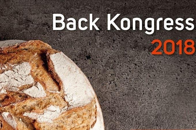 Back Kongress 2018. auf dem Bild ist ein rustikales Krustenbrot zu sehen, welches auf einer dunkel marmorierten Unterlage liegt. Dadrüber steht in weißen Druckbuchstaben Back Kongress. Unter dem weißen Schriftzug steht in roter schrift 2018.