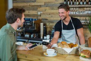 Ein Mann mit einem Smartphone in der Hand und ein Mann mit einem NFC Zahlungsgerät in der Hand. Sie stehen in einem Café mit Backwaren auf dem Tresen.