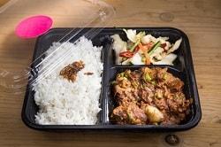 Auf dem Foto ist eine schwarze to-go-Verpackung zu sehen. Die Verpackung ist in drei Bereiche unterteilt. Links ist der größere Bereich, der mit Reis gefüllt ist. Rechts ist die zweite Hälfte in noch jeweils zwei Bereiche unterteilt. Im Vorderen befindet sich Fleisch, im Hinteren Salat. Oben links an der Ecke ist der durchsichtige Deckel der Snack-Verpackung zu erkennen.