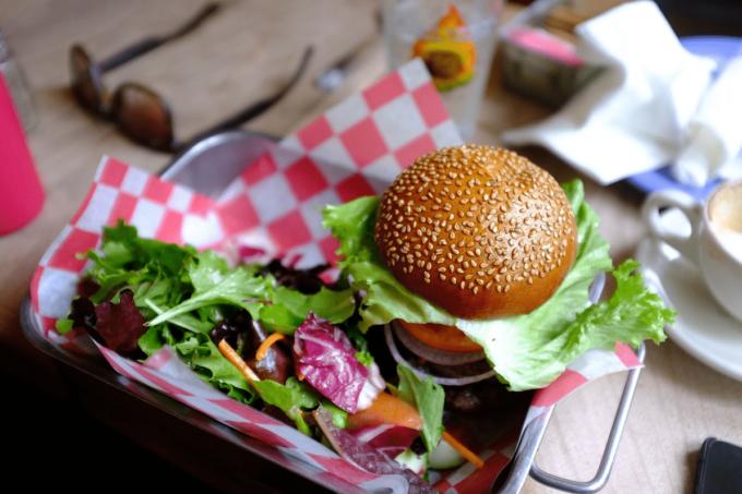 Auf dem Foto ist ein Burger mit einer Salatbeilage in einem Metallschüssel zu erkennen. Unter dem Burger und dem Salat befindet sich ein rot-karriertes Tuch oder eine Serviette, die den Snack und das Metall trennt. Das Burgerbrötchen ist braun und mit Sesamkörnern übersäht. Im Hintergrund liegt links eine Sonnenbrille, und rechts befindet sich ein Plastikbecher und zerknülltes Papier.