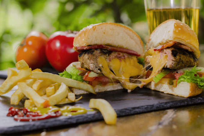 Auf dem Foto erkennt man einen in der Mitte aufgeschnittenen Burger, bei dem der geschmolzene Käse zwischen den Hälften zerläuft. Zusätzlich sind auf dem Burger noch ein Patty, Soßen und Salat drauf. Auf der schwarzen Platte, auf der der Burger liegt, befindet sich ebenfalls eine Portion Pommes, die dazu gereicht wird.