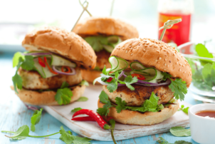 Drei Burger belegt mit Gurken, Zwiebeln, Salat und einer vegetarischen Bulette