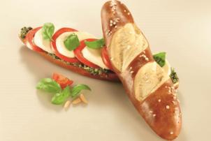 Auf dem Foto ist das Laugenbaguette von Ditsch angebildet. Die Backware ist mit abwechselnd mit Tomate und Mozzarella belegt und mit Basilikumblättern, die zur Dekoration dienen, versehen.