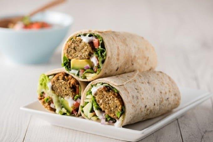 Drei Wraps auf einer Schale gefüllt mit Falafel, Avocado und Käse. Neben den Wraps ist eine Schale mit Sauce.
