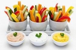 Auf dem Foto sind drei Behälter mit Gemüse Stäbchen aus Gurke, roter und gelber Paprika und Karotte zu sehen. Davor sind drei Schälchen mit Dip zu erkennen. Ganz Links ist ein hellrosaner Dip, in der Mitte ein weißer und ganz rechts ein gelber. Das Geschirr ist weiß und steht auch vor einem weißen Hintergrund.