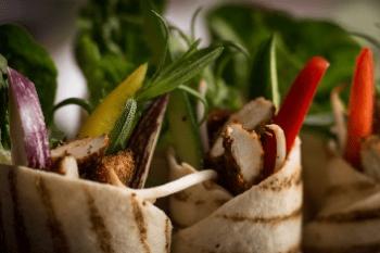 Auf dem Bild erkennt man zwei eingerollte Wraps von oben bis circa zur Mitte. Beide Wraps haben braune Grillstreifen an der Außenseite und sind prall gefüllt, unter anderem mit Salat, Rosmarin, roter und gelber Paprika, Zwiebeln und Hühnchen, welches durch die braune Farbe wohl vorher angebrannt wurde. Im Hintergrund erkennt man Salat.Die Wraps sind aus Tortillas gewickelt und vom Hersteller MTG Foodtrading.