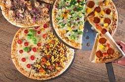 Auf dem Foto erkennt man verschiedene Möglichkeiten eines Pizzabelags. Es sind drei Pizzen zu sehen. Die rechte Pizza ist die oberste, die oben links die zweite im Stockwerk und unten links ist die letzte Pizza zu sehen. Die erste Pizza ist zur Hälfte belegt mit Salami, zur anderen Hälfte belegt mit etwas Grünem - es lässt sich schließen, dass es Gemüse ist. Die zweite Pizza ist belegt mit Thunfisch und roten Zwiebeln. Die letzte Pizza ist ebenfalls geteilt. Die rechts Hälfte ist belegt mit Hackfleisch und Mais, während Tomaten, Käse und Basilikum die linke Hälfte schmücken. Außerdem ist zu erkennen, dass aus der ersten Pizza ein Salamistück rausgeschnitten wurde, welches von einer Hand nun aus dem Bild gebracht wird. Das geschnittene Stück ist dreieckig und liegt auf einem gleichgrößen Stück Pappe.