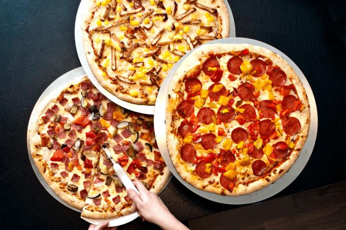 Auf dem Bild erkennt man drei sich überlappende Pizzen auf einem dunkelblauen Hintergrund. Die drei Pizzen bilden gemeinsam eine Dreieckige Form. Rechts ist eine runde Salami-Pizza zu sehen, die darüber ist eine Pizza, die mit Hühnchen und Ananas belegt zu sein scheint, und die letzte Pizza unten links ist mit Salami und noch weitere undefinierbaren Zutaten belegt. Aus dieser Pizza wird gerade von zwei Händen ein Stück hinausgeschnitten.