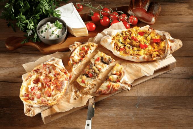 Drei verschiedene Varianten von Pide liegen auf dem Holzbrett auf einem Holztisch. Die Pide ist von Resch und Frisch, die ein großes Sortiment an Belagbariationen anbieten.