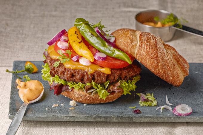 Der Homestyle Burger von Salomon mit Burgerbrot, Bulette, Salat, Tomaten, Zwiebeln, Schoten und einer Cocktail Creme.