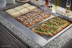 Auf dem Bild erkennt man drei verschiedene Pizzen, die auch jeweils anders geschnitten sind. Vorne rechts ist eine Pizza in P-Form geschnitten, welche mit Rucola und Tomaten belegt ist. In der Mitte ist eine Pizza zu sehen, die in sechs gleich große Quadrate geteilt ist. Die Pizza ist belegt mit Thunfisch und roten Zwiebeln. Die letzte und hinterste Pizza hat das selbe Schnittmuster wie die zweite pizza, ist jedoch mit ausgiebig viel Käse belegt. Die Pizzen befinden sich in einer Kantine oder in einem Bistro.