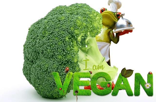 Auf dem Foto erkennt man Brokkoli, vor dem in grünen Buchstaben VEGAN steht. Hinter dem Brokkoli befindet sich ein Frosch, der als Kellner verkleidet ist.