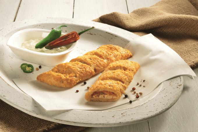 Ein Blätterteig-Snack mit Frischkäse und Peperoni gefüllt liegt auf einem weißen Teller. Die Frischkäse-Peperoni-Stange ist von dem Hersteller Wolf Butterback. Es liegen zwei Stangen auf dem Teller, wobei die eine aufgeschnitten wurde, sodass man einen Einblick in die cremige Füllung erhält. Links von der zweiten Stange steht eine Schale mit Frischkäse auf der noch jeweils eine rote und eine grüne Peperoni liegen.