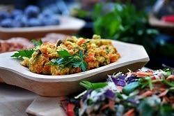 Ein Curry in einer snack to go Verpackung mit Salat als Dekoration im Vordergrund.