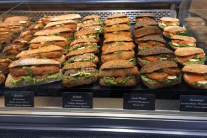 Auf dem Foto erkennt man eine Auslage in einer Bäckerei von vielen belegten Backwaren. Belegte Brötchen sind nach Brötchenart und Brötchenbelag hintereinander aufgestellt worden. Es sind vier Reihen von verschiedenen Brötchen zu erkennen.