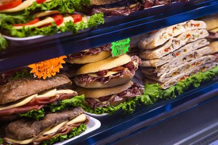 Es ist eine Auslage eines Bäckerei- oder Snack-Betriebes zu sehen. Auf weißen Tellern mit Salat liegen die bestrichenen und gefüllten Backwaren übereinander. Rechts sind gefüllte Fladenbrote zu erkennen, in der Mitte sind Weizenbrötchen zu sehen und links Vollkorncpaninis.