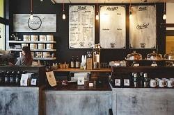 Auf dem Foto erkennt man einen Coffeeshop von vorne. Die Theke ist rechts und wirkt, als sei sie aus Stein. Dahinter befinden sich mittig und rechts des Betrachters Regale, ebenfalls wie rechts drei Regale, die übereinander hängen. Außerdem hängen an der Wand noch drei Tafeln, auf denen die Angebote wie Getränke, Snacks und Kaffee zu finden sind. Der Raum ist von einigen Lichtstrahlern beleuchtet, wirkt aber insgesamt dunkel, da de Wand schwarz gestrichen ist.