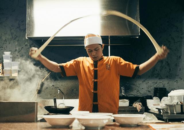 Delasia_Food Impact. Auf dem Bild ist ein asiatischen Gericht, auf einem weißen Teller angerichtet zu sehen. Es besteht aus buntem asiatischen Gemüse und Hühnchen Fleisch. Über dem Gericht ist ein grüner Banner in dem eine Bestellaktion wie folgt beschreiben wird: Aktion bis 30.11.2017: 60 kg frei Haus bestellen und einen 50 Euro Amazon Gutschein erhalten.