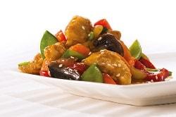 Delasia_Food Impact. Auf dem Bild ist ein asiatisches Gericht, auf einem weißen Teller angerichtet zu sehen. Es besteht aus buntem asiatischen Gemüse und Hühnchen Fleisch.
