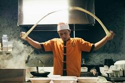 Delasia_Food Impact. Ein Asiatischer Koch steht in einer Küche und wirft gerade Nudelteig oder ähnliches als Band in der Luft herum. vor ihm stehen sechs Teller in zwei Reihen aufgestellt. Im Hintergrund Ist ein Wock auf einerHerdplatte zu sehen.