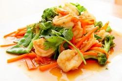 Delasia_Food Impact. Auf dem Bild ist ein asiatisches Gericht zu sehen, welches aud bunten asiatischen Gemüse und Garnelen besteht. Es ist in apetitlich angerichtet mit einer süß-sauren Soße und Koriander als Garnitur.