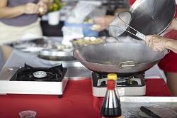 Delasia_Food Impact. Auf dem Bild ist ein Wok auf einer mobilen Kochplatte zu sehen. Im Vordergrund kann man eine Sojasoßenflasche erkennen. Vor dem Wok steht offensichtlich jemand, denn eine Kelle die andeutet in dem Wokzu rühren ist ebenfalls zu sehen.