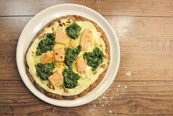 Auf dem Foto ist eine Pizza aus dem High Protein Teig des Herstellers Point of Food zu sehen, die mit einer gelben Sauce, Lachs und Spinat belegt ist. Die Pizza ist auf einem weißen Teller auf einem Holztisch.