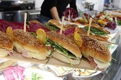 Electrolux_SpeeDelight. Mehrere längliche Sandwich-Brötchen mit Sesam bestreut. Sie haben Orangen Dekor und einen Piecer zum zusammenhalten.