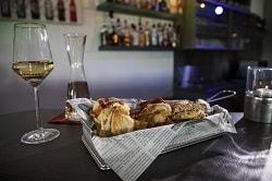 Auf dem Foto erkennt man die Gourmet-Stange des Herstellers Edna als Konfekt bzw. Fingerfood klein geschnitten. Der Raum ist eine Bar. Die Stange soll also das Konzept eines Bar-Snacks darstellen. Die Backwaren liegen in einem Körbchen, mit einer Serviertte in Zeitungs-Optik. Rechts daneben befindet sich ein Teelicht, links daneben ein halb eingeschenktes Weinglas und ein Weinkrug. Es ist Weißwein.