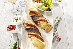 Die Gourmet-Stange des Herstellers Edna liegt auf einem weißen langen Teller. Es sind zwei Stangen aufgereiht. Dahinter befindet sich eine Schüssel mit Salat. Links und rechts vom Teller sind Dekorationen wie Rosmarin, Chillis, Knoblauch oder zwei kleine weiße Schalen mit Tomaten und einer weißen Zutat gefüllt. Oben links erkennt man die Hälse von zwei Weingläsern.