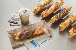 Auf dem Foto sind rechts auf einer Snack-Welle mehrere Gourmet-Stangen des Herstellers Edna aneinandergereiht. In der Mitte liegt eine Stage, die Mexiko-Stange, in einer to go Tüte. Die Tüte ist braun und aus Papier, jedoch ist die Vorderseite aus durchsichtiger Folie, sodass man die Stange erkennen kann. Darüber steht ein brauner to go Becher mit Kaffee gefüllt, ein Deckel liegt daneben und zwei Beutel Zucker.