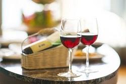 Hotellkongress_Auf dem Bild sind zwei mit Rotwein gefüllte Weingläser zu sehen, die auf einem Mamortisch stehen. im Hintergrund liegt die Weinflasche des Weines im Glas in einen hellbraunen Weidenkorb.