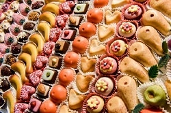 ISM-Süßwaren Messe_auf dem Bild ist mini Marzipan-Obst zu sehen. Dabei sind von links: Erdbeeren, Bananen, Mandarinen, Birnen, Äpfel. Das Bild ist sehr farbenfroh.
