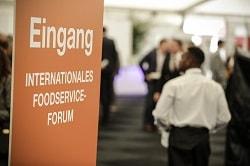 Internorga 2017_Auf dem Bild ist das Eingangsschild zum internationalen Foodservice raum der Internorga 2017 zu sehen. Etwas verschommen im Hintergrung läuft ein Kellner durch das Bild und Männer in Anzügen stehen in Gruppen und diskutieren.